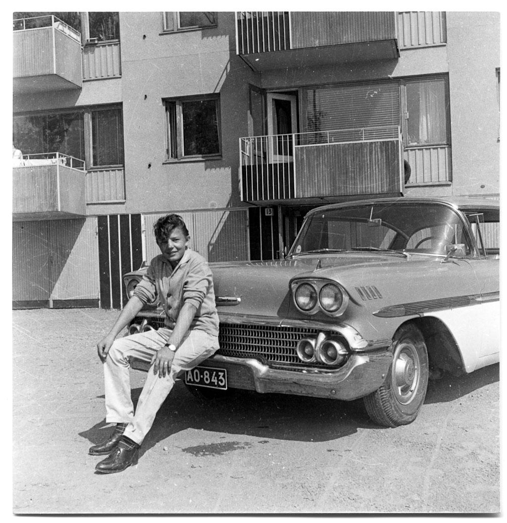 Pauli Virta poseeraa Olavin viimeisen auton '58 Bel-Air Hardtop Sedanin etupuskurilla Lauttasaaren-asunnon (Pajalahdentie 13) pihalla kesällä -60.